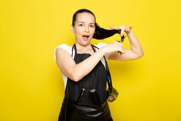 Eine junge friseurin der vorderansicht im schwarzen umhang des weißen t-shirts schneidet amüsiert lächelnd ihr haar