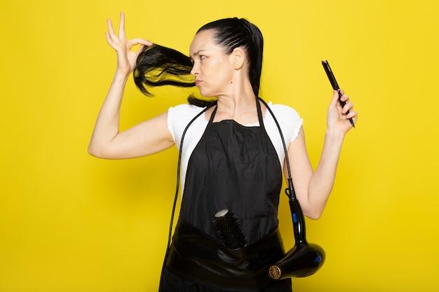Eine junge friseurin der vorderansicht im schwarzen umhang des weißen t-shirts schneidet ihr haar auf