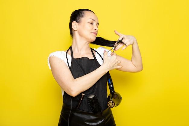 Eine junge friseurin der vorderansicht im schwarzen umhang des weißen t-shirts schneidet ihr haar lächelnd