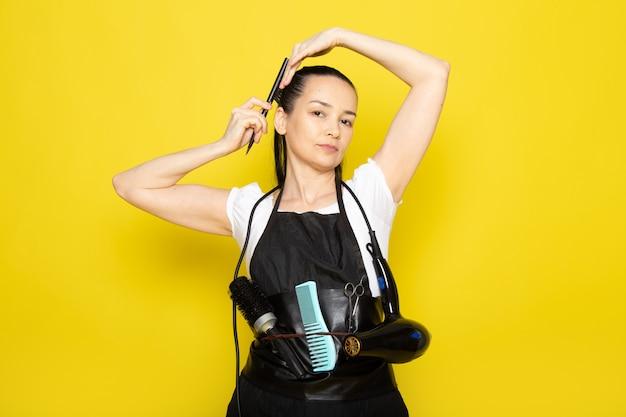 Eine junge friseurin der vorderansicht im weißen umhang des weißen t-shirts mit bürsten und fön, die ihr haar bürsten, das aufwirft