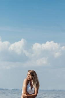 Eine junge gebräunte, schlanke, schöne blonde frau in einem weißen strickoberteil auf dem hintergrund des meereshimmels