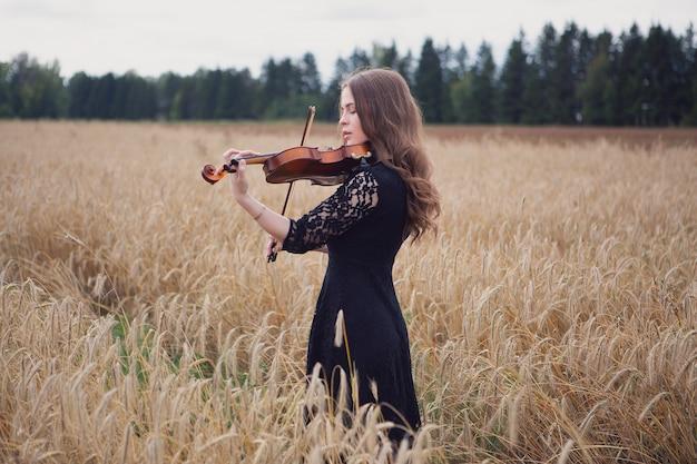 Eine junge geigerin spielt meisterhaft ihr instrument auf einem reifen weizenfeld