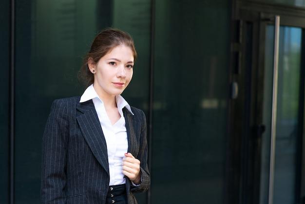 Eine junge geschäftsfrau kaukasischer abstammung in anzug und weißem hemd steht vor einem büro...