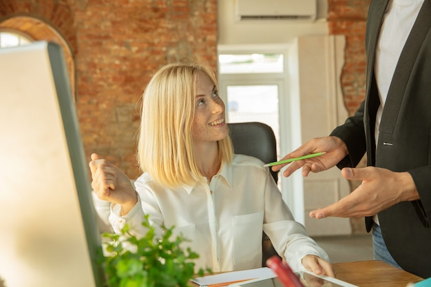 Eine junge geschäftsfrau zieht ins büro und bekommt einen neuen arbeitsplatz. junge büroangestellte trifft ihre kollegin oder arbeitskollegin nach der beförderung und nimmt hilfe entgegen. geschäft, lebensstil, neues lebenskonzept.