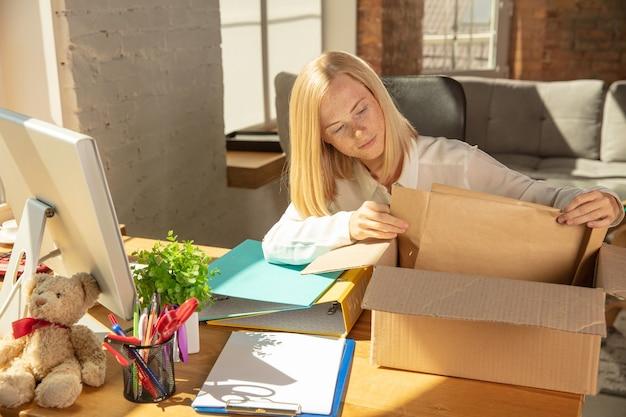 Eine junge geschäftsfrau zieht ins büro und bekommt einen neuen arbeitsplatz. junge kaukasische büroangestellte rüstet neues kabinett nach beförderung aus. kisten auspacken. geschäft, lebensstil, neues lebenskonzept.