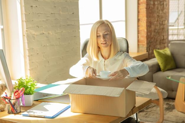 Eine junge geschäftsfrau zieht ins büro und bekommt einen neuen arbeitsplatz. junge kaukasische büroangestellte rüstet neues kabinett nach beförderung aus