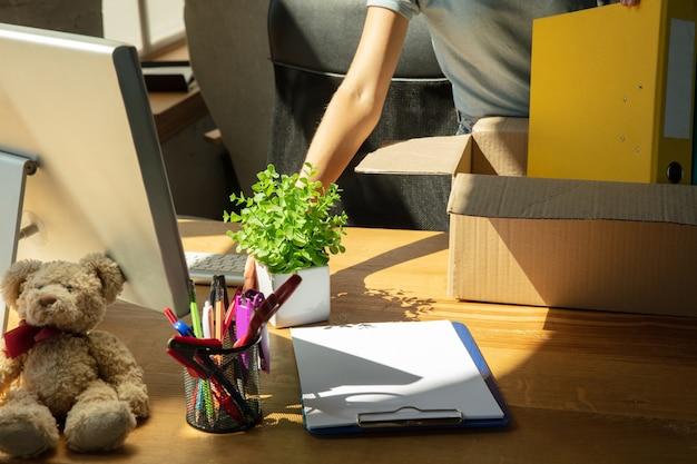 Eine junge geschäftsfrau zieht ins büro und bekommt einen neuen arbeitsplatz.