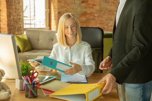 Eine junge geschäftsfrau zieht ins büro und bekommt einen neuen arbeitsplatz Kostenlose Fotos