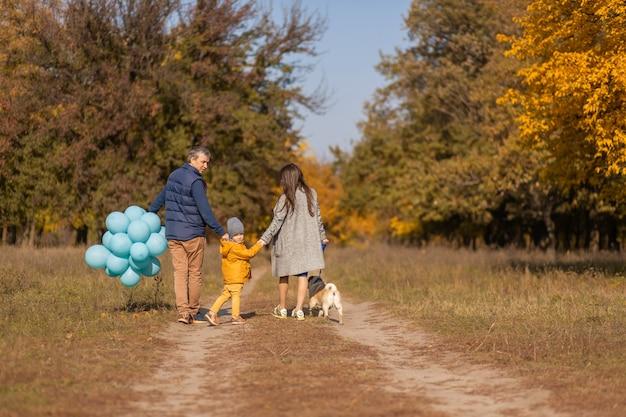 Eine junge glückliche familie mit einem kleinen kind und einem hund verbringt zeit miteinander für einen spaziergang im herbstpark.