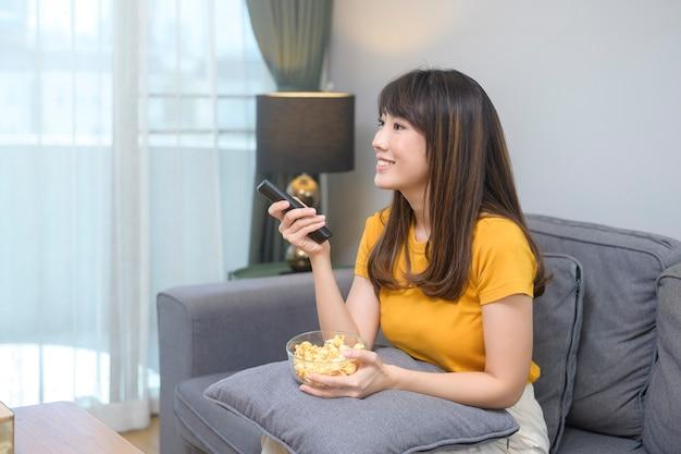 Eine junge glückliche frau, die einen film schaut und sich zu hause entspannt