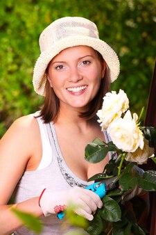 Eine junge glückliche frau, die im garten arbeitet und rosen pflegt