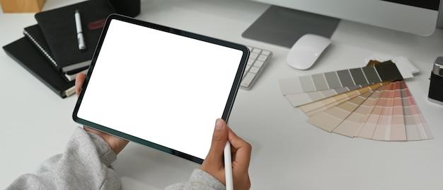 Eine junge grafikdesignerin hält einen stift und eine tablette auf einem weißen tisch