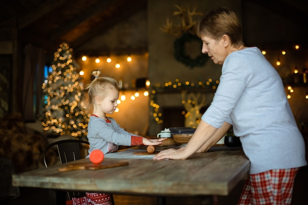 Eine junge großmutter und ihre reizende blonde enkelin kochen plätzchen zusammen in einem haus, das für weihnachten verziert wird.