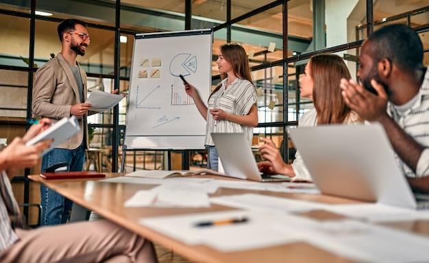 Eine junge gruppe von geschäftsleuten diskutiert einen neuen geschäftsplan an einer tafel und arbeitet an laptops, während sie in einem modernen büro sitzen.