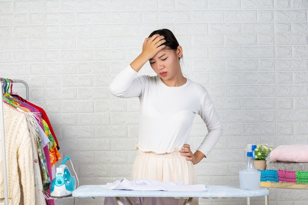 Eine junge hausfrau, die sich mit ihrem bügeln auf einem weißen backstein langweilt.