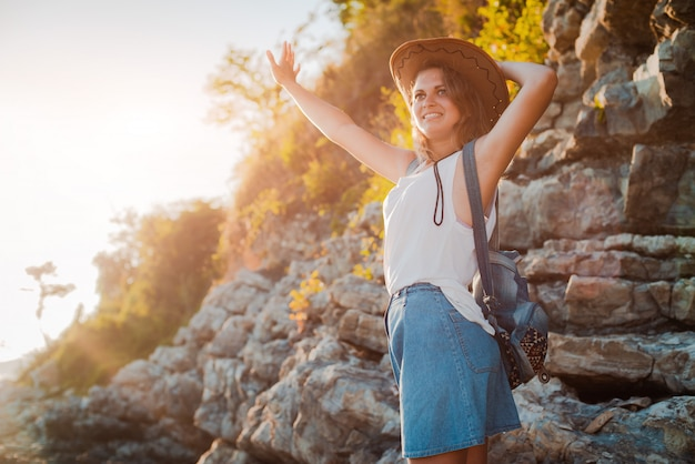 Eine junge hippie-frau in einem hut und einem rukzak mit ihren händen oben