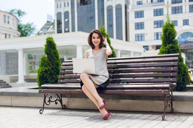 Eine junge hübsche brünette geschäftsfrau sitzt auf der bank in der stadt. sie trägt ein graues und schwarzes kleid und vionus-absätze und hat weinige lippen.