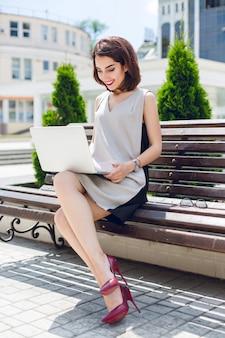 Eine junge hübsche brünette geschäftsfrau sitzt auf der bank in der stadt. sie trägt ein graues und schwarzes kleid und weinige absätze. sie tippt auf einem laptop.