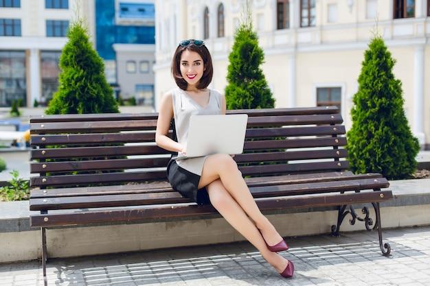 Eine junge hübsche brünette geschäftsfrau sitzt mit laptop auf der bank in der stadt. sie trägt ein graues und schwarzes kleid und weinige absätze.