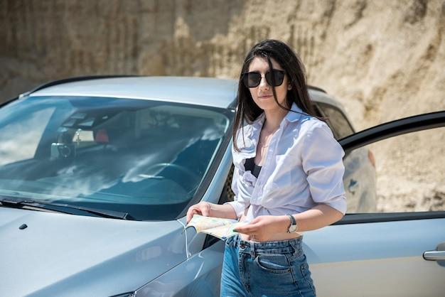 Eine junge hübsche dame steht neben ihrem auto und sucht nach dem besten weg auf der karte