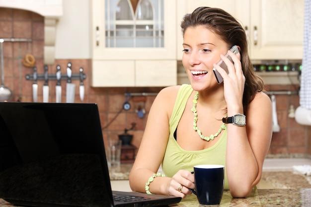 Eine junge hübsche frau, die in der küche telefoniert und am laptop arbeitet