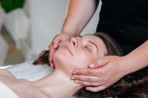 Eine junge hübsche frau genießt eine professionelle kopfmassage im spa