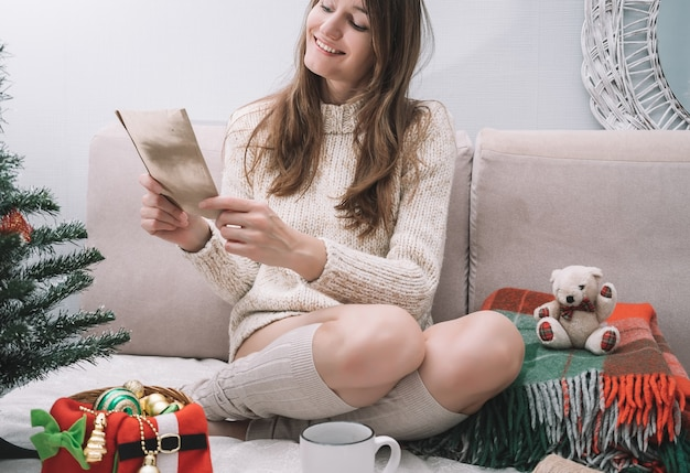 Eine junge hübsche frau in einem leichten pullover sitzt auf einem bett mit weihnachtsschmuck und liest einen brief