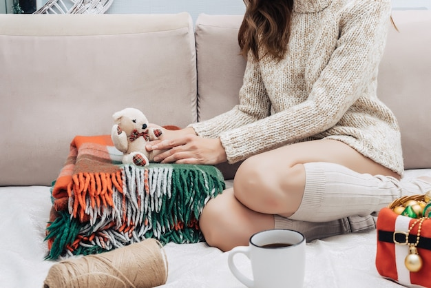 Eine junge hübsche frau in einem leichten pullover sitzt auf einem bett mit weihnachtsschmuck