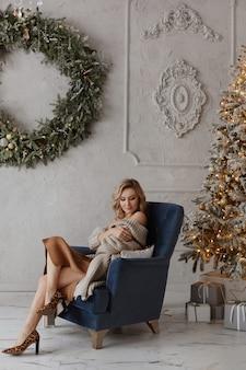 Eine junge hübsche frau in stylischer kleidung und modischen schuhen sitzt in einer deko neben dem weihnachtsbaum...