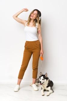 Eine junge hübsche frau in voller länge mit ihrem hund