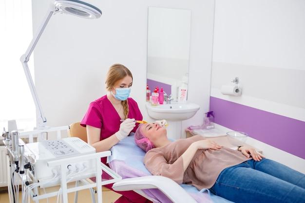 Eine junge hübsche frau kam in einen schönheitssalon und berät sich mit einer kosmetikerin zu anti-aging-verfahren. kosmetikkonzept, gesichtspeeling