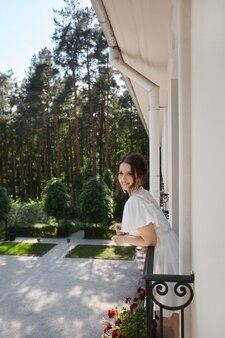 Eine junge hübsche frau mit brautfrisur im seidenkleid posiert morgens auf dem balkon...