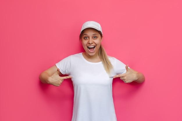 Eine junge hübsche kaukasische glücklich fröhliche aufgeregte lächelnde blonde frau mit weißer lässiger t-shirt-kappe, die mit den fingern zeigt, die leeren kopienraum auf einer hellen rosa wand zeigen