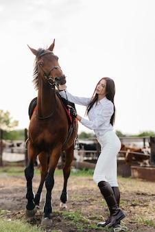 Eine junge hübsche reiterin posiert in der nähe eines vollbluthengstes auf einer ranch. reiten, pferderennen.