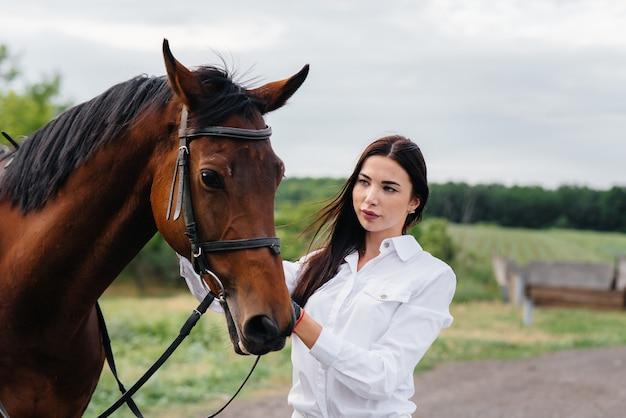 Eine junge hübsche reiterin posiert in der nähe eines vollbluthengstes auf einer ranch