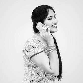 Eine junge indische frau, die am telefon spricht