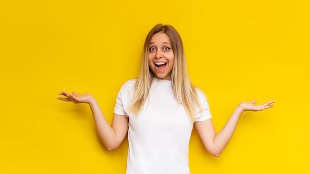 Eine junge kaukasische erstaunte hübsche, charmante blonde frau in einem weißen t-shirt lächelt und breitet die hände mit zweifeln isoliert auf einer leuchtend gelben wand aus