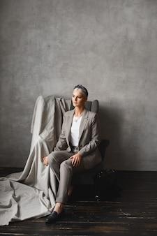 Eine junge kaukasische frau mit blonden haaren, die beiseite schaut, während sie im sessel sitzt, wunderschöne junge geschäftsfrau in stilvollem anzug, die in einem leeren innenraum posiert