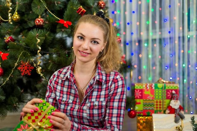 Eine junge kaukasische frau mit einem geschenk nahe dem weihnachtsbaum