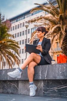 Eine junge kaukasische geschäftsfrau in der pause von der arbeit in einem schwarzen blazer und weißen turnschuhen. vorbereitung des nächsten treffens mit einem kaffee und der geflügelten roten tasche