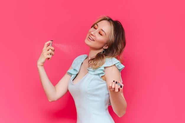 Eine junge kaukasische hübsche, fröhliche braunhaarige frau mit geschlossenen augen in einem hellblauen, stylischen kleid, die eine parfümflasche in der hand hält und sie auf ihren hals an einer hellrosa wand aufträgt