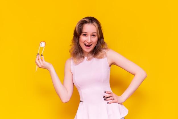 Eine junge kaukasische ziemlich glücklich aufgeregt lächelnde braunhaarige frau in einer hellrosa bluse wirbt für sushi, das in bambusstöcken hält, rollen philadelphia einzeln auf einer hellen gelben wand?