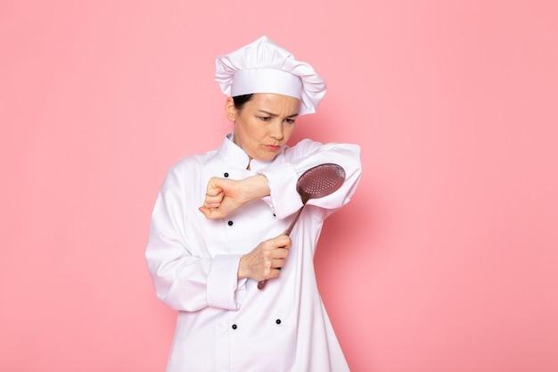 Eine junge köchin der vorderansicht in der weißen kappe des weißen kochanzugs, die den großen silbernen löffel hält, missfiel