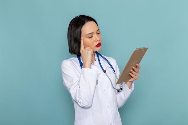 Eine junge krankenschwester der vorderansicht im blauen stethoskop des weißen medizinischen anzugs, der notizblock auf dem blauen schreibtischmedizinkrankenhausarzt hält