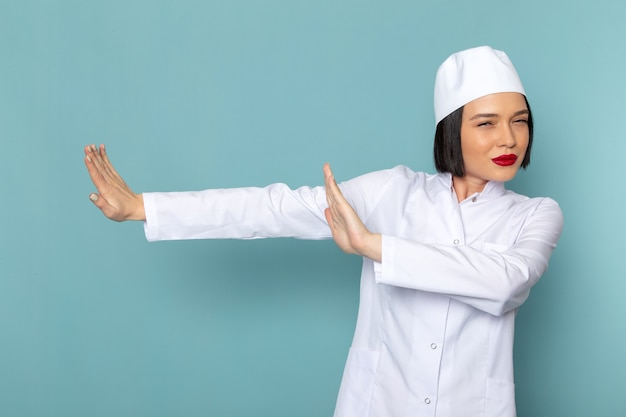 Eine junge krankenschwester der vorderansicht im weißen medizinischen anzug, der abstand auf dem medizinischen krankenhausarzt des blauen schreibtisches hält