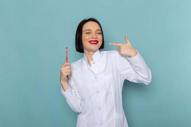 Eine junge krankenschwester der vorderansicht im weißen medizinischen anzug, der auf dem blauen schreibtischmedizinkrankenhausarzt lächelt
