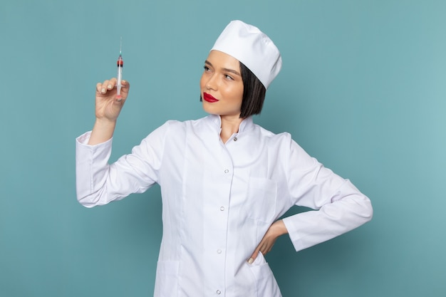 Eine junge krankenschwester der vorderansicht im weißen medizinischen anzug, der injektion auf dem blauen krankenhausmedizin-krankenhausarzt hält