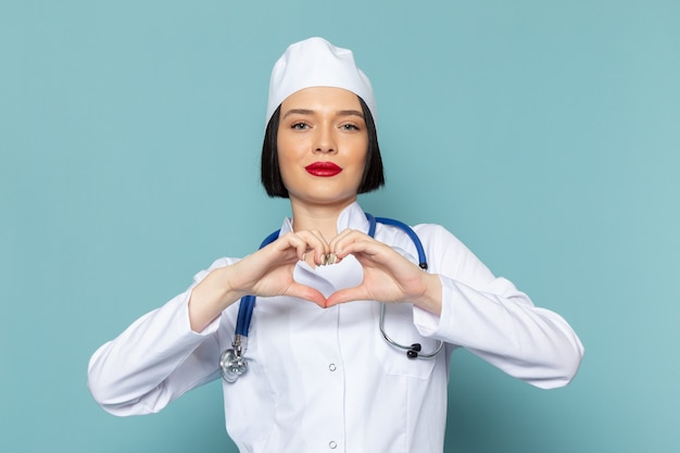Eine junge krankenschwester der vorderansicht im weißen medizinischen anzug und im blauen stethoskop, das herzzeichen auf dem blauen schreibtischmedizin-krankenhausarzt zeigt