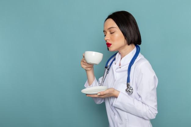 Eine junge krankenschwester der vorderansicht im weißen medizinischen anzug und im blauen stethoskop, das tee trinkt