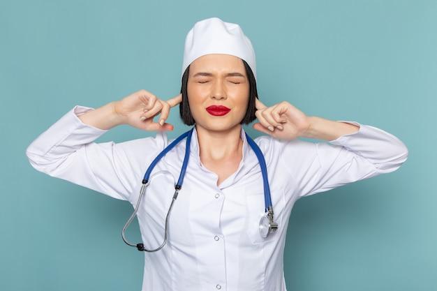 Eine junge krankenschwester der vorderansicht im weißen medizinischen anzug und im blauen stethoskop, die ihre ohren bedecken